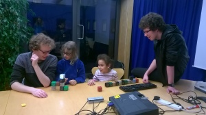 Two young girls are trying out the tactile programming language as two undergraduate students look on